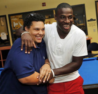 Kris Minnis, left, and Foster Riley laugh together at the Memorial Park club location, 3535 N. Western Ave., of the Boys & Girls Clubs of Oklahoma County in Oklahoma City, Wednesday, July 2, 2014. The club is still recovering from a flood during a recent thunderstorm. Minnis, who formerly worked at the club, has raised Riley as her own son. Photo by Nate Billings, The Oklahoman