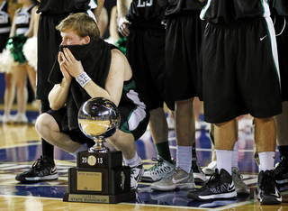 Bishop McGuinness' Greg Roberts (10) kneels next to the runner-up silver ball after the Class 5A boys championship high school basketball game in the state tournament at the Mabee Center in Tulsa, Okla., Saturday, March 9, 2013. Tulsa Memorial defeated Bishop McGuinness, 59-42. Photo by Nate Billings, The Oklahoman