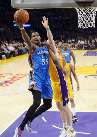 Oklahoma City Thunder forward Kevin Durant, left, puts up a shot as Los Angeles Lakers center Chris Kaman defends during the first half of an NBA basketball game Thursday, Feb. 13, 2014, in Los Angeles. (AP Photo/Mark J. Terrill)