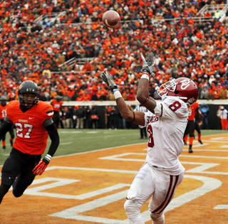 Oklahoma's Jalen Saunders (8) catches the go-ahead touchdown in front of Oklahoma State's Lyndell Johnson (27) in the fourth quarter during the Bedlam college football game between the Oklahoma State University Cowboys (OSU) and the University of Oklahoma Sooners (OU) at Boone Pickens Stadium in Stillwater, Okla., Saturday, Dec. 7, 2013. OU won, 33-24. Photo by Nate Billings, The Oklahoman