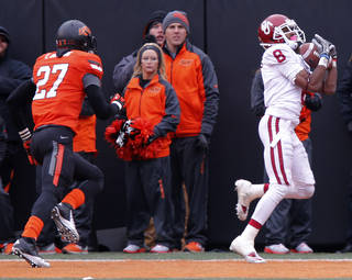 Oklahoma's Jalen Saunders (8) makes the go ahead touchdown catch in front of Oklahoma State's Lyndell Johnson (27) during the Bedlam college football game between the Oklahoma State University Cowboys (OSU) and the University of Oklahoma Sooners (OU) at Boone Pickens Stadium in Stillwater, Okla., Saturday, Dec. 7, 2013. Photo by Chris Landsberger, The Oklahoman