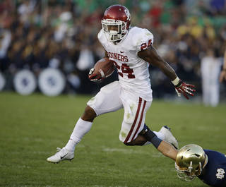 Oklahoma's Brennan Clay (24) runs out of the tackle of Notre Dame's Austin Collinsworth (28) during the second half of an NCAA college football game on Saturday, Sept. 28, 2013, in South Bend, Ind. Oklahoma defeated Notre Dame 35-21. (AP Photo/Darron Cummings) ORG XMIT: INDC115