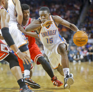 Oklahoma City Thunder's Reggie Jackson, right, turns the corner on Chicago Bulls' Jimmy Butler in the second quarter during their preseason NBA basketball game in Wichita, Kan., Wednesday, Oct. 23, 2013. (AP Photo/The Wichita Eagle, Fernando Salazar)