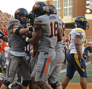 CELEBRATION: Oklahoma State's Charlie Moore (17) celebrates after a touchdown with Oklahoma State's Blake Jackson (18) as West Virginia's Doug Rigg (47) during a college football game between Oklahoma State University (OSU) and West Virginia University at Boone Pickens Stadium in Stillwater, Okla., Saturday, Nov. 10, 2012. Oklahoma State won 55-34. Photo by Bryan Terry, The Oklahoman