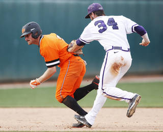 TCU second baseman Garrett Crain (34) tags out Oklahoma State base runner Saulyer Saxon (3) during a college baseball game between Texas Christian (TCU) and Oklahoma State in the championship of the Big 12 baseball tournament at the Chickasaw Bricktown Ballpark in Oklahoma City, Sunday, May 25, 2014. Texas Christian defeated Oklahoma State 7-1 to win the Big 12 championship