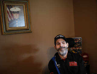 Scott Bates smiles as he talks about designing NASCAR car decals. in Muskogee, Okla., Tuesday, Oct. 29, 2013. His U.S. Marine portrait hangs on the wall. Photo by Sarah Phipps, The Oklahoman
