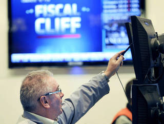 "James Dresch, of MND Partners Inc., works on the floor of the New York Stock Exchange in New York on Nov. 7. Stocks on Friday showed slight gains as renewed efforts got under way in Washington to resolve the impending ""fiscal cliff."" AP FILE PHOTO"