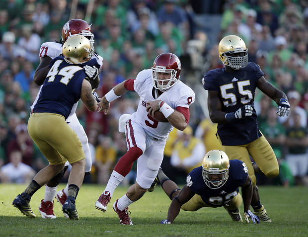 photo - Oklahoma's Trevor Knight (9) runs during the second half of an NCAA college football game against Notre Dame, Saturday, Sept. 28, 2013, in South Bend, Ind. Oklahoma defeated Notre Dame 35-21. (AP Photo/Darron Cummings)  ORG XMIT: INDC119