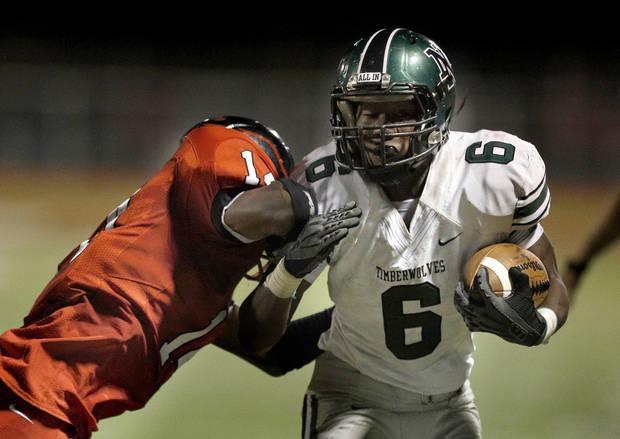 photo - Norman North's Z'Quan Hogan is pushed out of bounds by Del City's Deonte Reid during the high school football game between Norman North and Del City at Del City, Okla., Friday, Sept. 13, 2013. Photo by Sarah Phipps, The Oklahoman