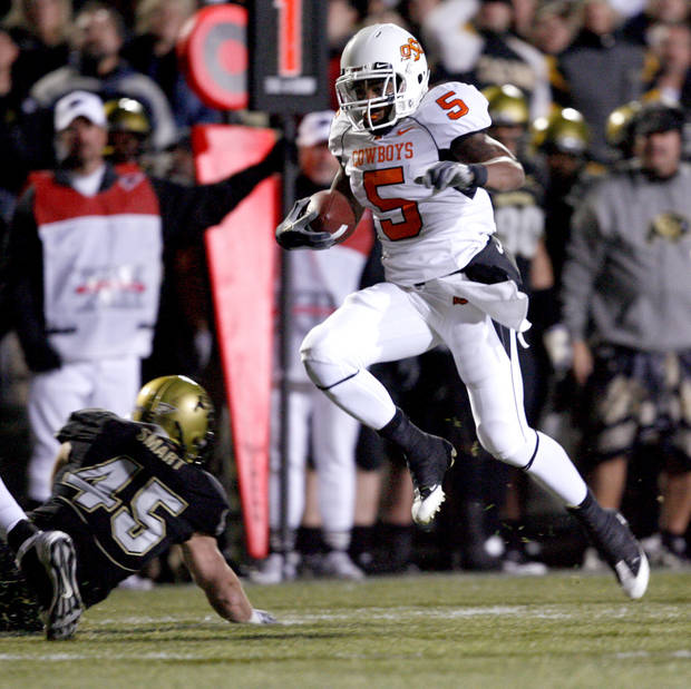 photo - OSU's Keith Toston leaps to try to get by Colorado's Jeff Smart during the college football game between Oklahoma State University and the University of Colorado at Folsom Field in Boulder, Colo., Saturday, Nov. 15, 2008. BY BRYAN TERRY, THE OKLAHOMAN