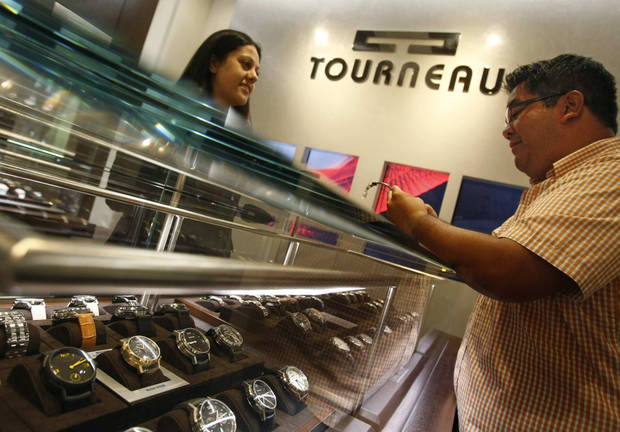 photo - Watches are bigger and flashier than ever. Some do far more than tell time, and many are used as much for decor as to tell time. Here, Joanne Sawaya helps customer Dan Knickerbocker, right, at the Tourneau watch store at South Coast Plaza in Costa Mesa, California. (Don Bartletti/Los Angeles Times/MCT)