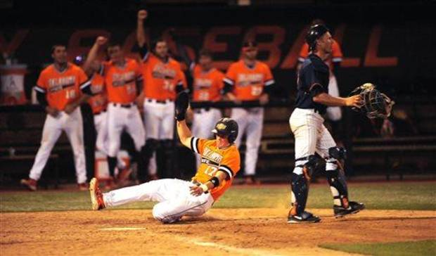 photo - Oklahoma State bench celebrates as left fielder Gage Green, left, slides past Fullerton catcher Jared Deacon, into home plate during the seventh inning of an NCAA college baseball regional tournament game in Stillwater, Okla, Sunday, June 1, 2014. (AP Photo/Brody Schmidt)