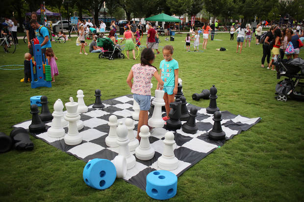 Children play a game of lawn chess on the Devon Great Lawn during the Summer Solstice celebration at the Myriad Botanical Gardens, Thursday, June 21, 2018. Photo by Doug Hoke,The Oklahoman