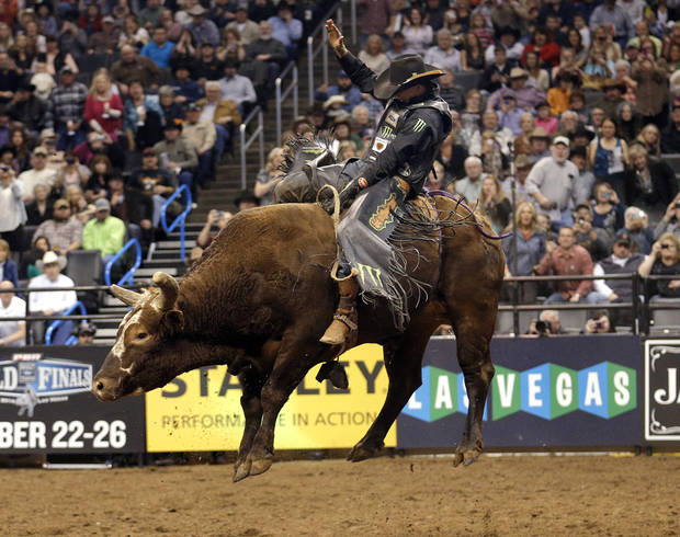 photo - J.B. Mauney rides Bushwacker during the Express Employment Professionals Invitational PBR  event at the Chesapeake Energy in Oklahoma City, Saturday, Jan. 25, 2014.  Photo by Sarah Phipps, The Oklahoman