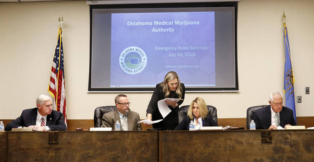 Julie Ezell distributes copies of two amendments to members of the Board of Health. From left are Tom Bates, interim commissioner for the Oklahoma Department of Health; Timothy Starkey, board president; Dr. Jenny Alexopulos, and Dr. Edward Legako, board vice-president. The Oklahoma State Department of Health voted at their monthly meeting Tuesday morning, July 10, 2018, to ban sales of smokeable forms of medical marijuana and to require dispensaries to hire a pharmacist. [Photo by Jim Beckel, The Oklahoman]