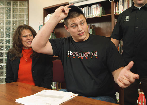 photo - Norman North football player Colton Cline, next to his mother Melissa Auld, reaches for a pen to sign a letter of intent to play for Sam Houston State in the high school's library on Wednesday, Feb 3, 2010, in Norman, Okla. Photo by Steve Sisney, The Oklahoman