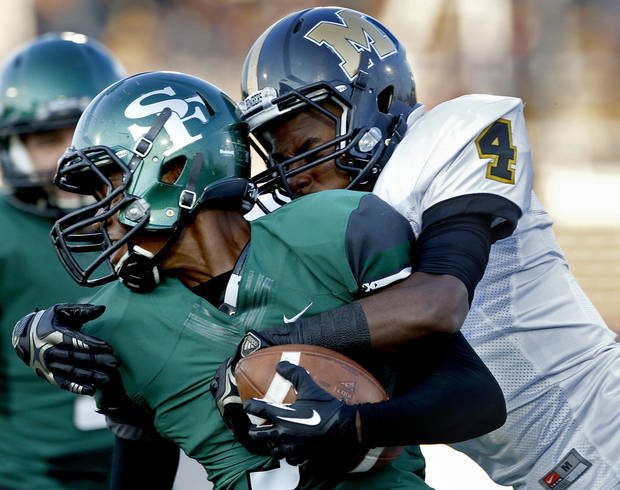 photo - Midwest City's KeSean Brown brings down Edmond Santa Fe's Aaron Jones during the high school football game between Edmond Santa Fe and Midwest City at Wantland Stadium in Edmond, Okla., Thursday, Sept. 5, 2013. Photo by Sarah Phipps, The Oklahoman
