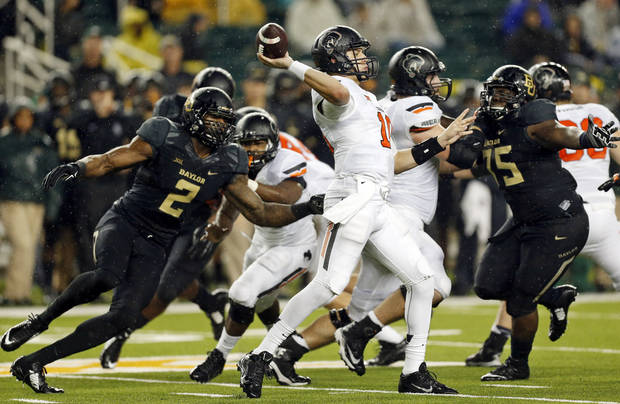 Oklahoma State's Mason Rudolph passes in the third quarter as Baylor's Shawn Oakman tries to sack Rudolph on Saturday. The Bears had three sacks in their 49-28 victory.                     Photo by Nate Billings, The Oklahoman