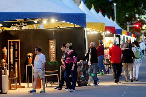 People look at artwork displayed in rows of tents along Colcord Drive at the 2019 Festival of the Arts in Bicentennial Park in downtown Oklahoma City, Thursday, April 25, 2019. [Doug Hoke/The Oklahoman Archives]