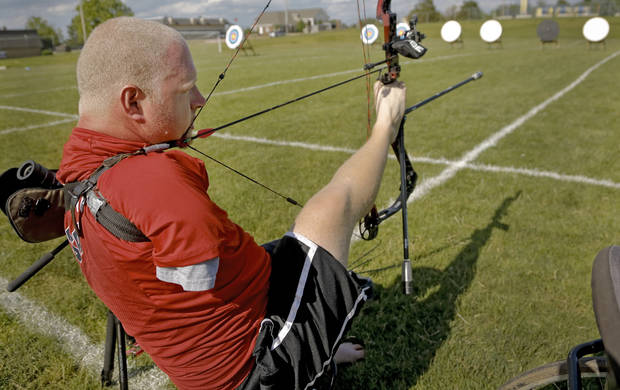 photo - Matt Stutzman, known as the Armless Archer uses his feet to take aim as he prepares to take part in the archery event during the Endeavor Games at the University of Central Oklahoma on Friday, June 7, 2013 in Edmond, Okla.  Photo by Chris Landsberger, The Oklahoman