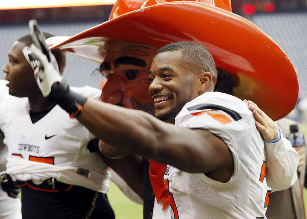 photo - Oklahoma State's Jeremy Smith (31) waves to fans next to mascot Pistol Pete as the Cowboys sing their alma mater after the AdvoCare Texas Kickoff college football game between the Oklahoma State University Cowboys (OSU) and the Mississippi State University Bulldogs (MSU) at Reliant Stadium in Houston, Saturday, Aug. 31, 2013. OSU won, 21-3. Photo by Nate Billings, The Oklahoman