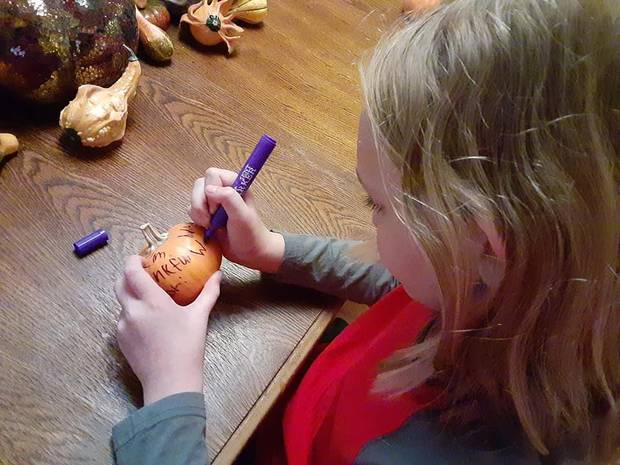 Brenna McDonnell, 10, daughter of Features Writer Brandy McDonnell, writes on a Thankful Pumpkin. [Brandy McDonnell/The Oklahoman]