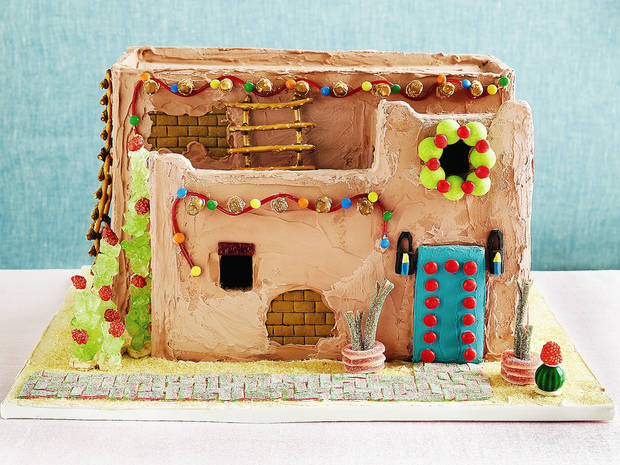 "photo - This pueblo gingerbread house from ""The Gingerbread Architect"" features green rock candy, cacti with burnt peanut blooms, pretzel stick ladders, adobe colored icing and ""bricks"" etched into the unbaked gingerbread. Photo by Alexandra Grablewski"