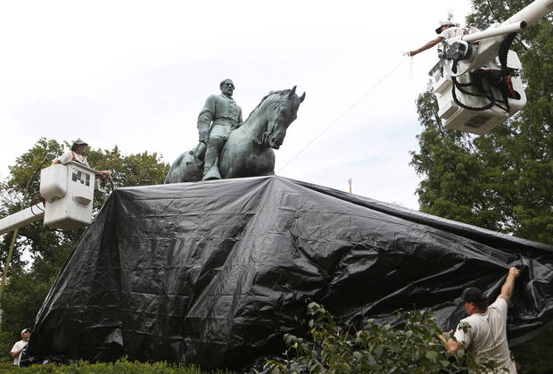 City workers drape a tarp over the statue of Confederate General Robert E. Lee on Wednesday in Emancipation Park in Charlottesville, Va. The move intended to symbolize the city's mourning for Heather Heyer, killed while protesting a white nationalist rally earlier this month. (AP Photo/Steve Helber)