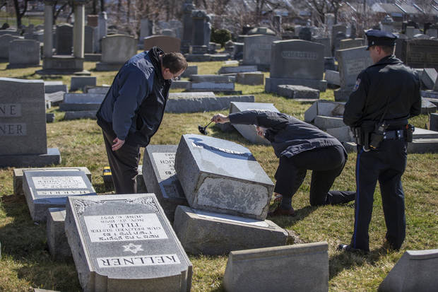 Northeast Philadelphia Police Detective Timothy McIntyre, center, dusts for fingerprints one of the headstones that were knocked down as Detective Nick McReynolds, left, looks on at Mount Carmel Cemetery in Philadelphia on Sunday, Feb. 26, 2017. More than 100 headstones have been vandalized at the Jewish cemetery in Philadelphia, damage discovered less than a week after similar vandalism in Missouri, authorities said. (Michael Bryant/The Philadelphia Inquirer via AP)