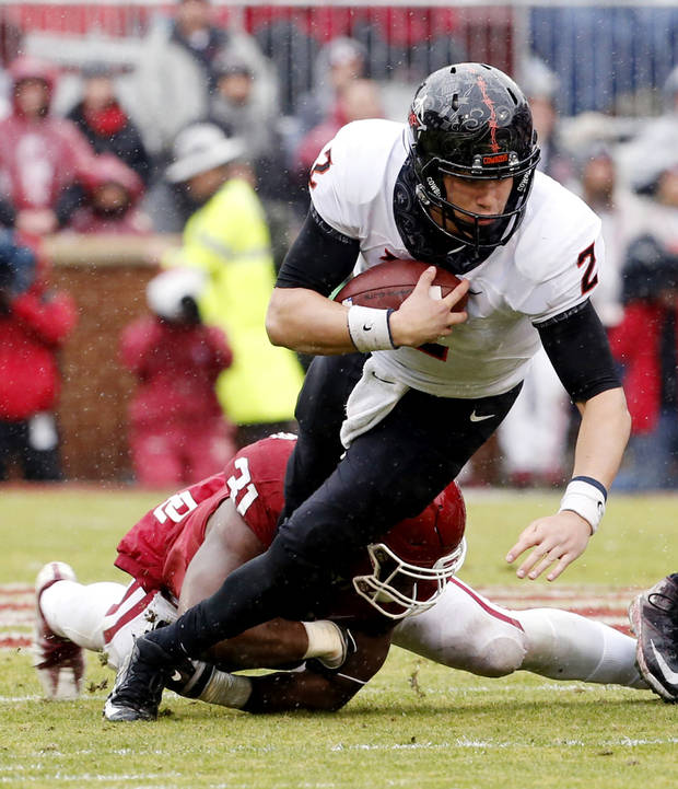 Oklahoma State's Mason Rudolph (2) is tackled by Oklahoma's Ogbonnia Okoronkwo (31) during the Bedlam college football game between the Oklahoma Sooners (OU) and the Oklahoma State Cowboys (OSU) at Gaylord Family - Oklahoma Memorial Stadium in Norman, Okla., Saturday, Dec. 3, 2016. Photo by Steve Sisney, The Oklahoman