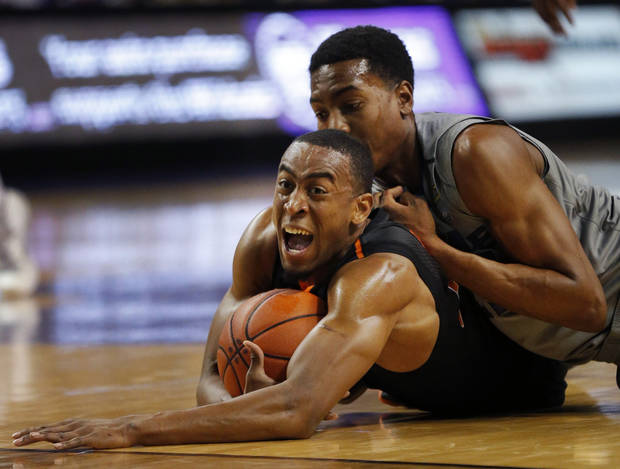 photo - Oklahoma State guard Markel Brown, bottom, dives for the ball with Kansas State forward Wesley Iwundu, top, during the second half of an NCAA college basketball game in Manhattan, Kan., Saturday, Jan. 4, 2014. Kansas State defeated Oklahoma State 74-71. (AP Photo/Orlin Wagner)