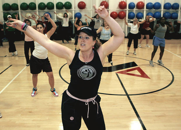 photo - Aerobics instructor Kelly Harris leads a Zumba class at the Edmond YMCA. PHOTO BY John Clanton, The Oklahoman
