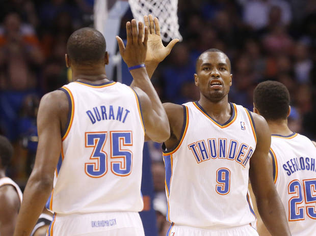 photo - Oklahoma City Thunder forward Serge Ibaka (9) high fives teammate Kevin Durant (35) in the first quarter of an NBA basketball game against the Sacramento Kings in Oklahoma City, Sunday, Jan. 19, 2014. (AP Photo/Sue Ogrocki)