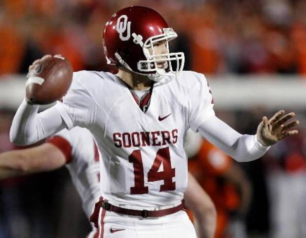 photo - Oklahoma's  Sam  Bradford (14) has his left thumb taped up as he looks to throw the ball during the first half of Bedlam at Boone Pickens Stadium on Saturday, Nov. 29, 2008, in Stillwater, Okla. STAFF PHOTO BY CHRIS LANDSBERGER
