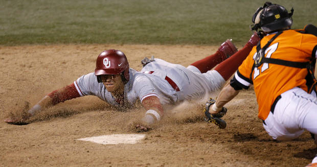 photo -                    OU's Hector Lorenzana, left, slides home past OSU's Gage Green in the 18th inning of the Sooners' 12-9 nonconference win on Tuesday night is Stillwater.                                                                             Photo by Bryan Terry, The Oklahoman