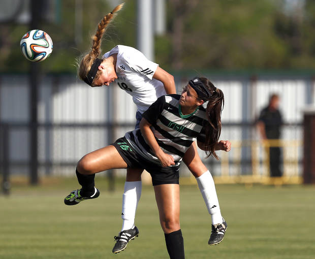 photo - Norman North's Luka Joyner heads a ball as Bishop MicGuiness' Quincy Plank defends during the high school girls soccer between Bishop McGuinness and Norman North at Norman North High School in Norman, Okla., Friday, May 9, 2014. Photo by Sarah Phipps, The Oklahoman