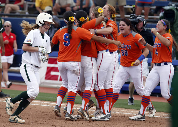 photo - Florida celebrates their win in front of Baylor's Robin Landrith (17) during of the Women's College World Series softball tournament game between Baylor University and University of Florida at ASA Hall of Fame Stadium in Oklahoma City, Sunday, June 1, 2014. Photo by Sarah Phipps, The Oklahoman