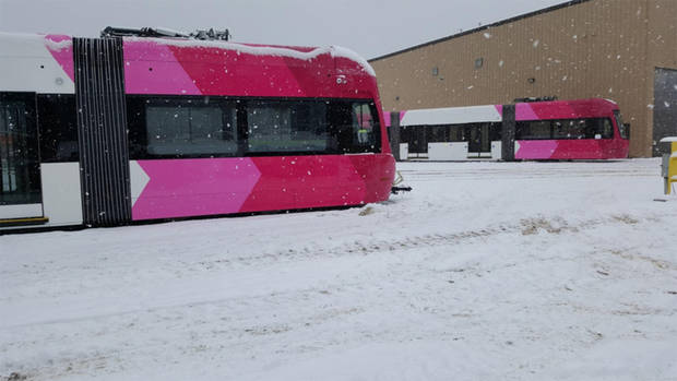 "Oklahoma City's first two streetcars will be shipped soon from the manufacturing plant in western Pennsylvania, where they were photographed as snow fell. Cars No. 1 and 2 are in the ""redbud"" color scheme. [City of Oklahoma City/JACOBS/Brookville Equipment Corp.]"