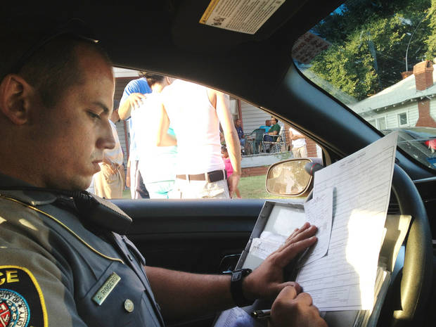 Oklahoma City police officer Adam Rogers fills out a police incident report during a Sept. 11 call in northeast Oklahoma City. During a patrol for about three hours the evening of Wed., Sept. 11, Rogers responded to a number of calls. Among the incidents that required police response were a call regarding an elderly man who had died, a 911 call regarding an assault with a deadly weapon, a report of men harassing women from a parking lot and a report of juveniles fighting in an apartment complex. Photo by Juliana Keeping, The Oklahoman