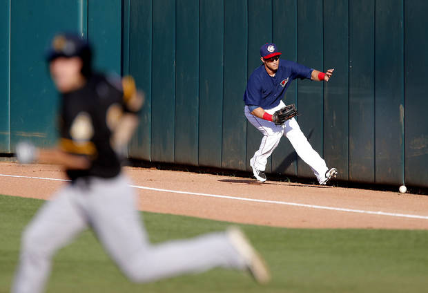 photo - Preston Tucker  of the Oklahoma City RedHawks chases down a ball as a runner for the Salt Lake Bees advances to second base in the first inning of a baseball game at Chickasaw Bricktown Ballpark in Oklahoma City, Thursday, June 12, 2014. Photo by Bryan Terry, The Oklahoman
