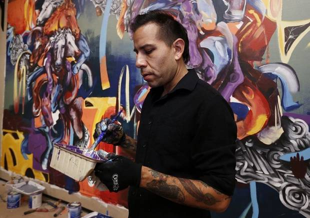 Native artist Yatika Fields paints a mural at the Sam Noble Oklahoma Museum of Natural History on Friday, March 16, 2018 in Norman, Okla. [The Oklahoman Archives]