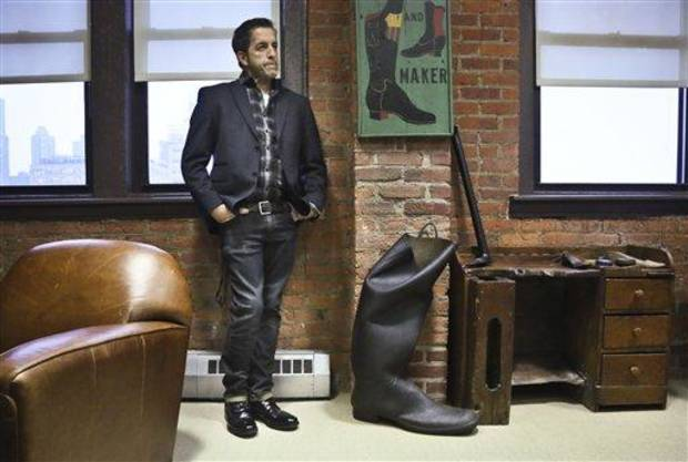 photo - This Jan. 29, 2013 photo shows designer Kenneth Cole in his office during an interview in New York. Cole returns to New York Fashion Week Thursday, Feb. 6, after a seven-year hiatus, seemingly putting his hand on everything before the runway lights go up: the clothes, the shoes, the handbags, the hashtags. He bought his company back from investors last year, and it's once again privately owned with Cole fully in charge.   (AP Photo/Bebeto Matthews)