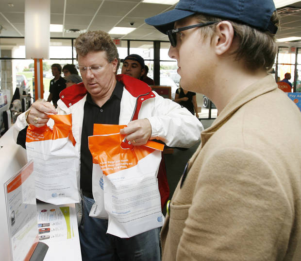 John E. Wolf III, left, collects his sacks containing his IPhone and accessories next to his son Blake Wolf after buying an iPhone during the debut of the iPhone in the AT&T store at 6959 NW Expressway in Oklahoma City, Friday, June 29, 2007. [THE OKLAHOMAN ARCHIVES]