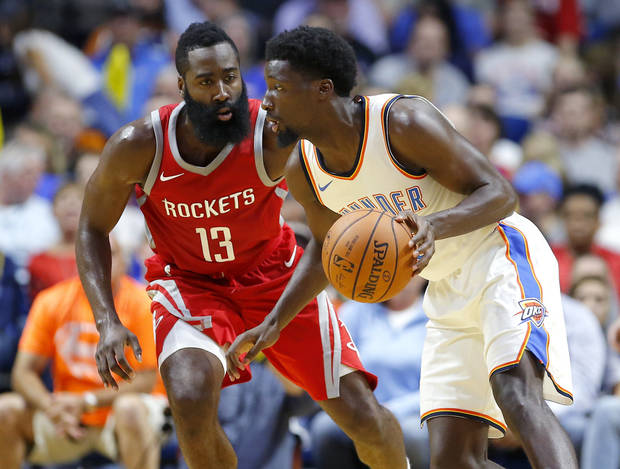 Oklahoma City's Daniel Hamilton (25) tries to get past Houston's James Harden (13) during a preseason NBA basketball game between the Oklahoma City Thunder and the Houston Rockets at the BOK Center in Tulsa, Tuesday, Oct. 3, 2017. Photo by Bryan Terry, The Oklahoman