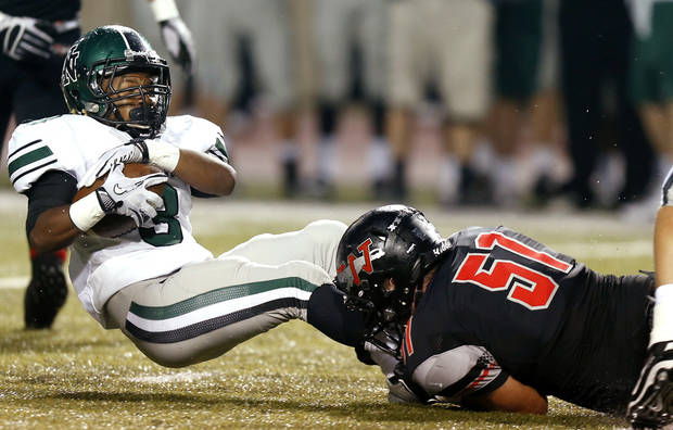 photo - Norman North's Bryan Payne is brought down by Westmoore's Zach Clark during a high school football game in Moore, Okla., Thursday, September 13, 2012. Photo by Bryan Terry, The Oklahoman