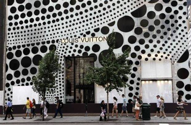 photo - Pedestrians walk in front of Louis Vuitton's flagship Fifth Avneue store in New York, Tuesday, July 10, 2012, before the company unveiled windows and a collection collaboratively designed by Japanese artist Yayoi Kusama and  Vuitton creative director Marc Jacobs.  (AP Photo/Kathy Willens)