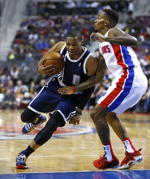photo - Oklahoma City Thunder guard Russell Westbrook, left, makes a drive on Detroit Pistons guard Brandon Jennings, right, in the first half of an NBA basketball game in Detroit, Friday, Nov. 8, 2013. (AP Photo/Paul Sancya)