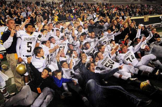photo - The Kingfisher Yellowjackets celebrate with the gold ball trophy after winning the 3A state high school football championship game against the Blanchard Lions at Boone Pickens Stadium in Stillwater, Okla., Friday, Dec. 19, 2013. Kingfisher won, 30-23.  Photo by KT King/For the Oklahoman