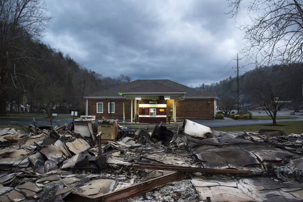 The remains of Creek Place Efficiencies in front of an unharmed BB&T bank in Gatlinburg, Tenn., Wednesday, Nov. 30, 2016. Tornadoes that dropped out of the night sky killed several people in two states and injured at least a dozen more early Wednesday, adding to a seemingly biblical onslaught of drought, flood and fire plaguing the South.  (Andrew Nelles/The Tennessean via AP)