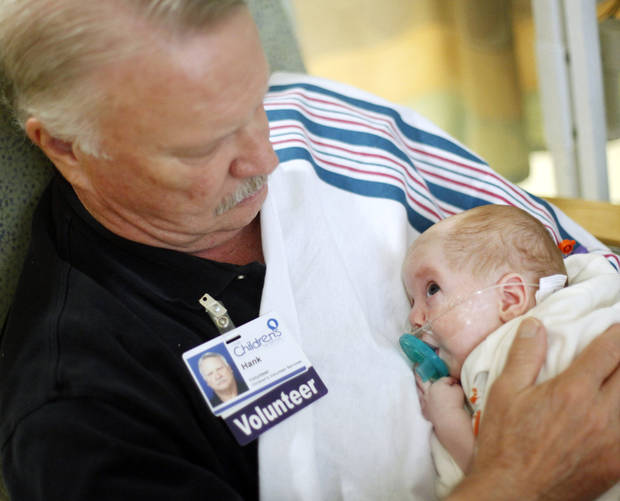 photo - Hank Kuhlman, 67 of Oklahoma City, cuddles with 100 day old baby Bentley Hammond at The Children's Hospital at OU Medical Center in the NICU on June 11, 2014. Kuhlman volunteers for hours each week to give premature babies human contact. Photo by KT King/The Oklahoman